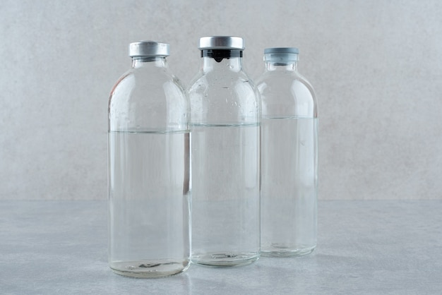 Trzy butelki medycznego etanolu na szarym tle. zdjęcie wysokiej jakości