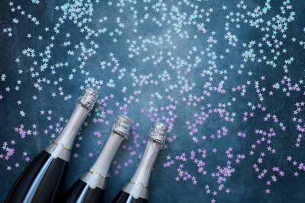 Trzy butelki szampana z holograficznymi gwiazdami konfetti na niebiesko. skopiuj miejsce, widok z góry