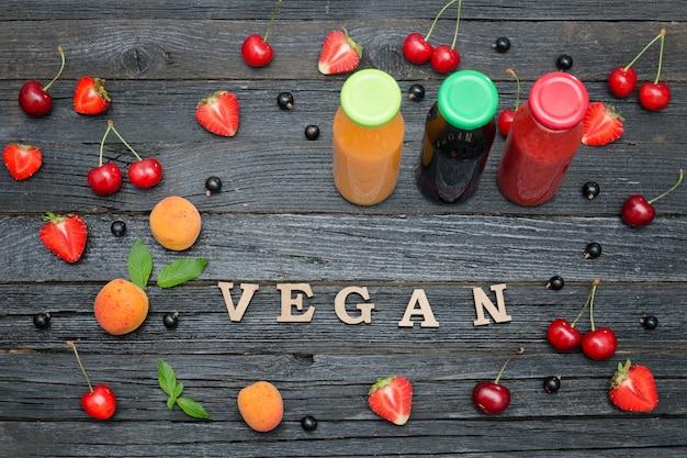 Trzy butelki z sokiem, owocami i napisem wegańskie.