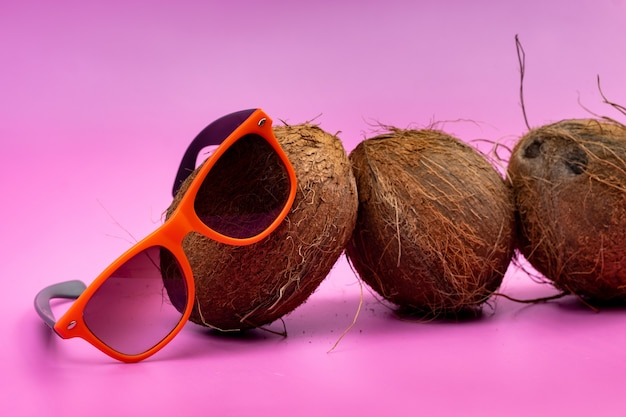 Trzy całe kokosy i pomarańczowe szklanki na różowym tle