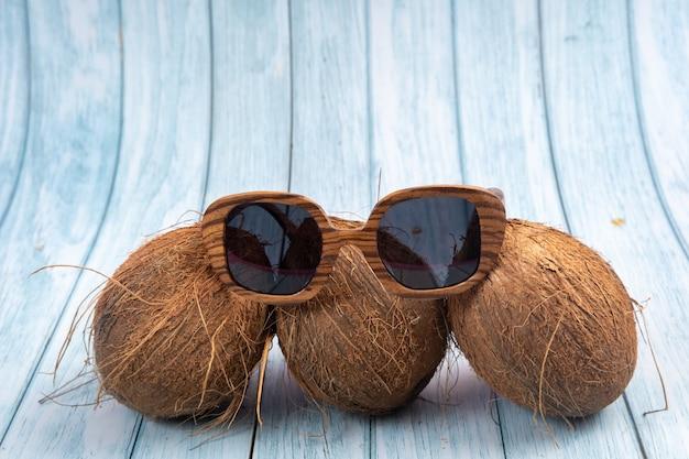 Trzy całe orzechy kokosowe i drewniane szklanki na niebieskim tle drewnianych.