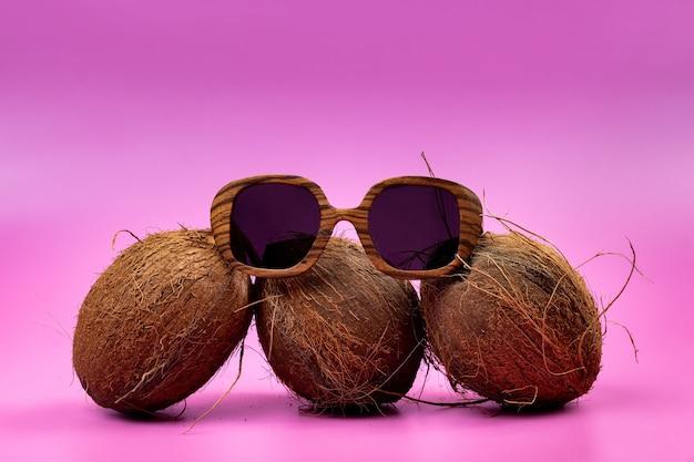 Trzy całe orzechy kokosowe i drewniane szklanki na różowym tle.