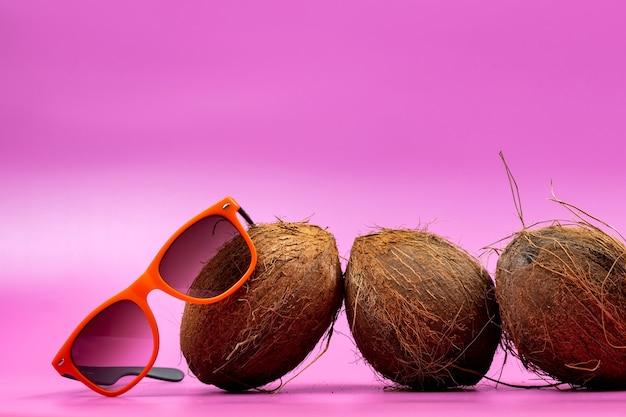 Trzy całe orzechy kokosowe i pomarańczowe szklanki na różowym tle.