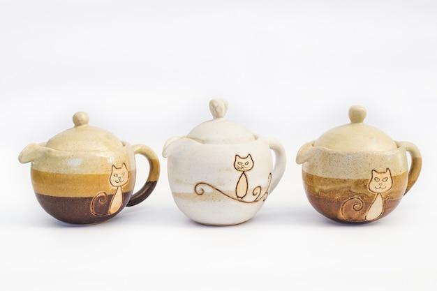Trzy ceramiczne kamionki czajniki z białym tłem