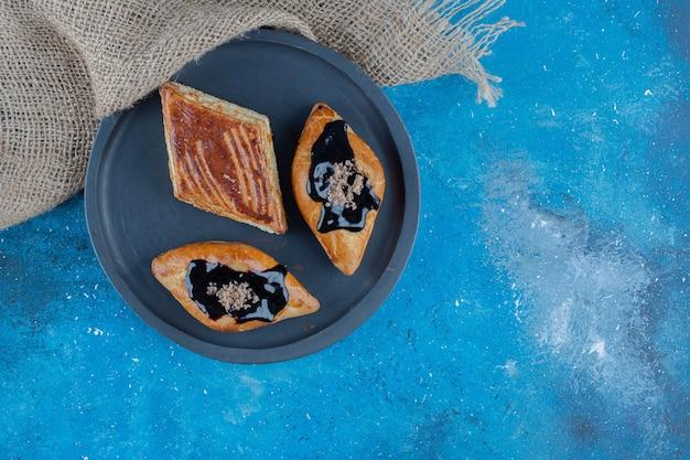 Trzy ciasteczka na planszy obok ręcznika, na niebieskim tle. wysokiej jakości zdjęcie