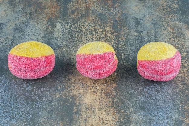 Trzy ciasteczka w kształcie brzoskwini, na marmurowej powierzchni.