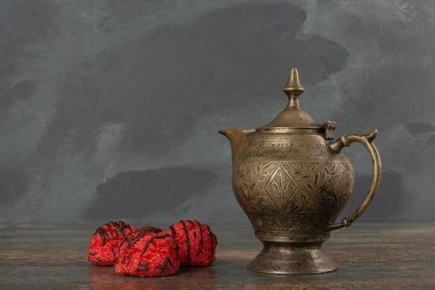 Trzy cukierki ze starożytnym czajnikiem na marmurowym stole.