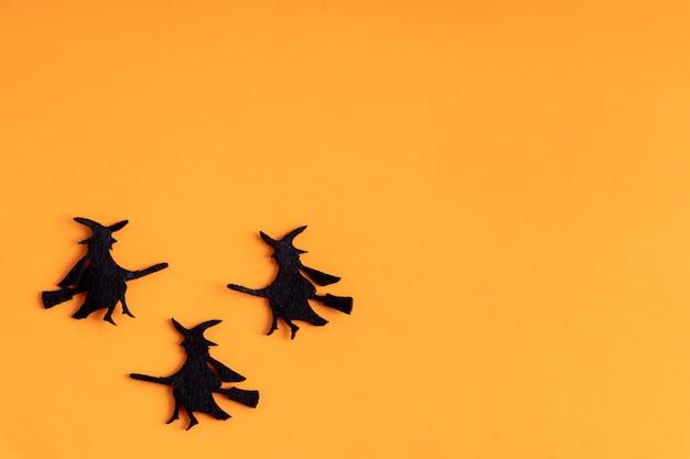 Trzy czarne czarownice na pomarańczowym tle halloween