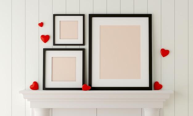 Trzy czarne ramki na zdjęcia umieszczone na kominku w białym pokoju z mini czerwonym sercem.