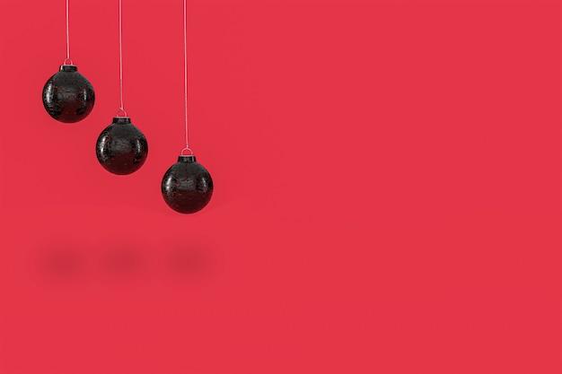 Trzy czarne szklane bombki wiszące z czerwonym tłem. wesołych świąt bożego narodzenia koncepcja