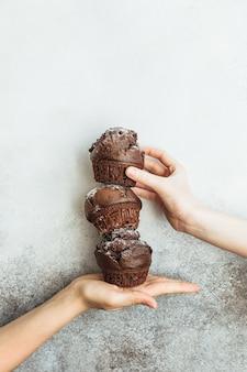 Trzy czekoladowe babeczki stoją w kolumnie na dłoni