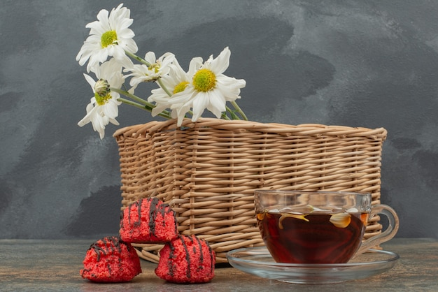 Trzy czerwone cukierki z koszem bukietu i gorącą herbatą.