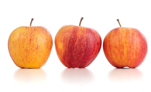 Trzy czerwone i żółte jabłka na białym tle