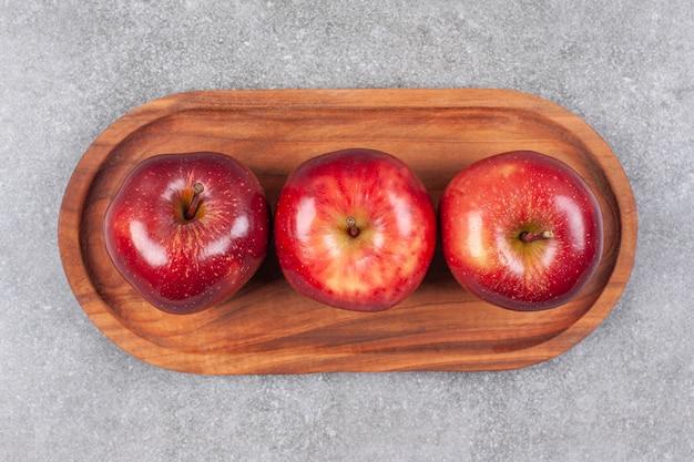 Trzy czerwone jabłka na drewnianym talerzu
