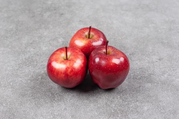 Trzy czerwone jabłka na marmurowej powierzchni