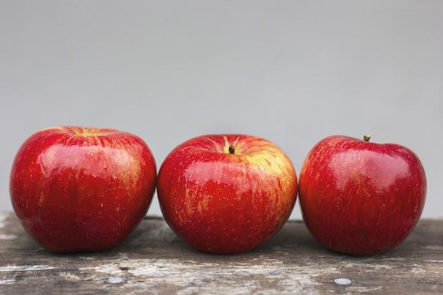 Trzy czerwone jabłka na szarej ścianie