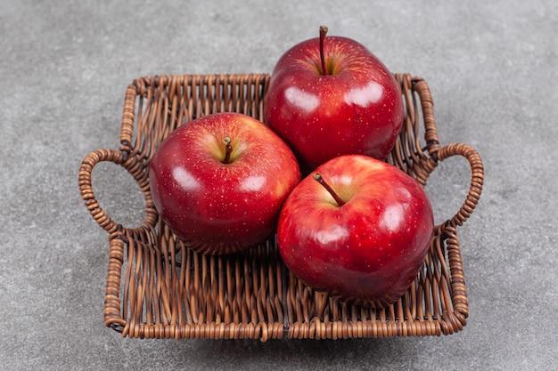 Trzy czerwone jabłka w drewnianym koszu
