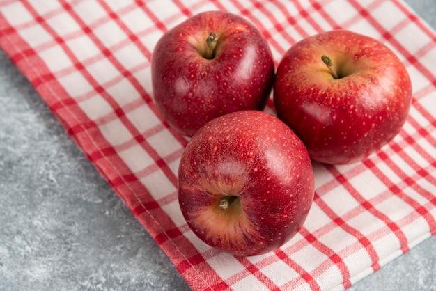Trzy czerwone jabłka z pasiastym obrusem na marmurowej powierzchni.