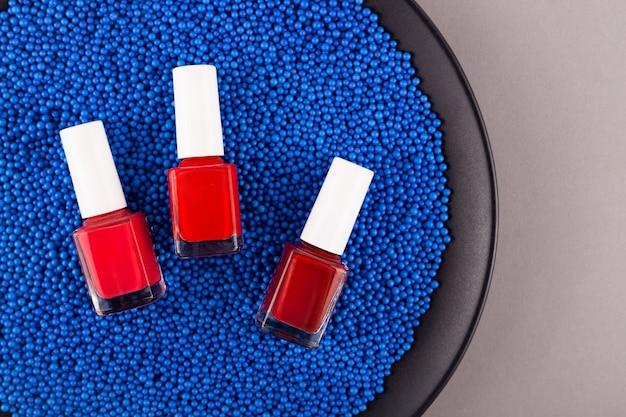 Trzy Czerwone Lakiery Do Paznokci Na Niebieskim Tle Plastikowych Kulek Tekstury Zdjęcie Wysokiej Jakości Premium Zdjęcia