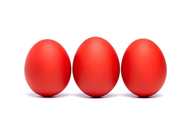Trzy czerwone pisanki na białym tle