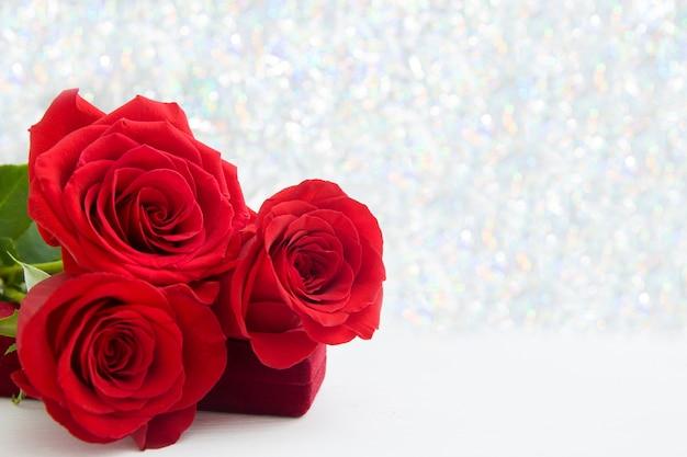 Trzy czerwone róże i pudełko na prezent z biżuterią w tle