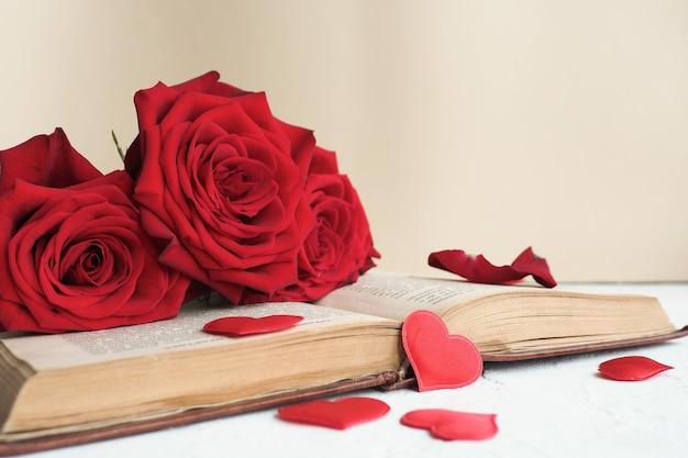 Trzy czerwone róże na otwartej starej książce na stole i dużo czerwonych serc.
