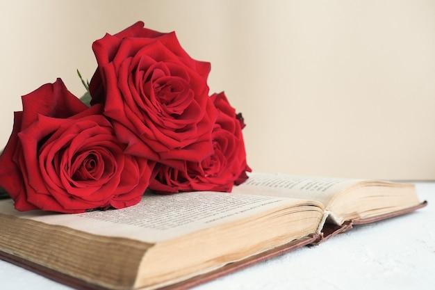 Trzy czerwone róże na otwartej starej książce na stole
