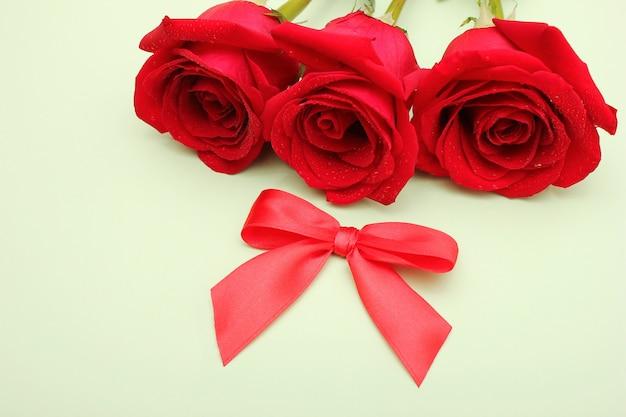 Trzy czerwone róże z kroplami wody na nich i czerwona kokarda