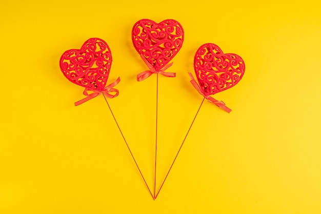 Trzy czerwone rzeźbione dekoracje domu w kształcie serca r. na jasnym żywym żółtym tle