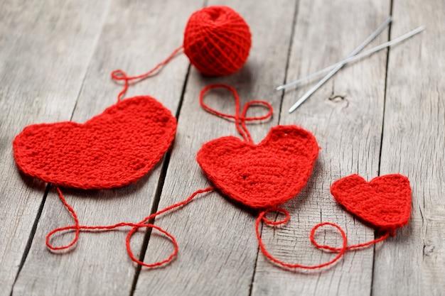 Trzy czerwone serca z dzianiny, symbolizujące miłość i rodzinę. relacje rodzinne, więzi.