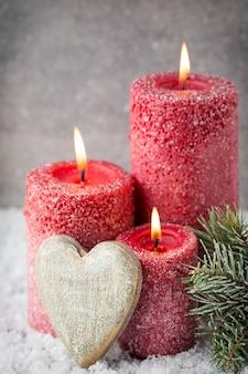 Trzy czerwone świece na szarym tle, świąteczne dekoracje. nastrój adwentowy.