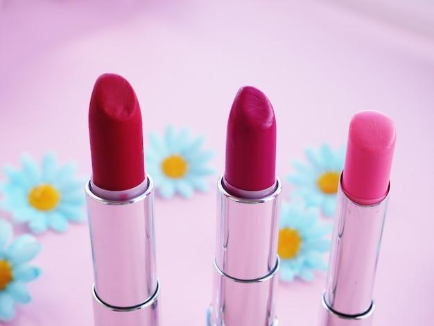 Trzy czerwone szminki na różowej powierzchni kosmetyki dla kobiet