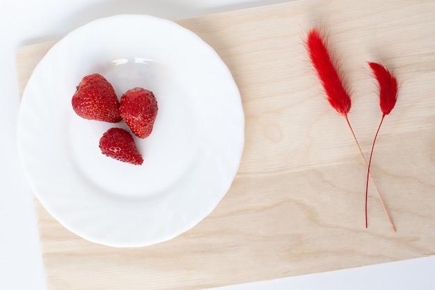 Trzy czerwone truskawki na białym talerzu na brązowej drewnianej desce do krojenia; dwa czerwone suszone bukiety kwiatów naturalnych lagurus ovatus.
