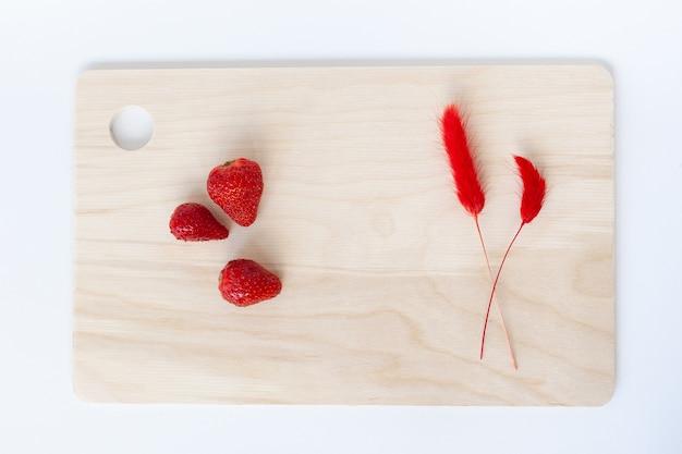 Trzy czerwone truskawki na jasnobrązowej drewnianej kuchennej desce do krojenia; dwa czerwone suszone bukiety kwiatów naturalnych lagurus ovatus