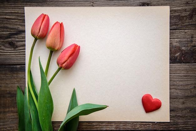 Trzy czerwone tulipany i małe czerwone serce na kartce papieru