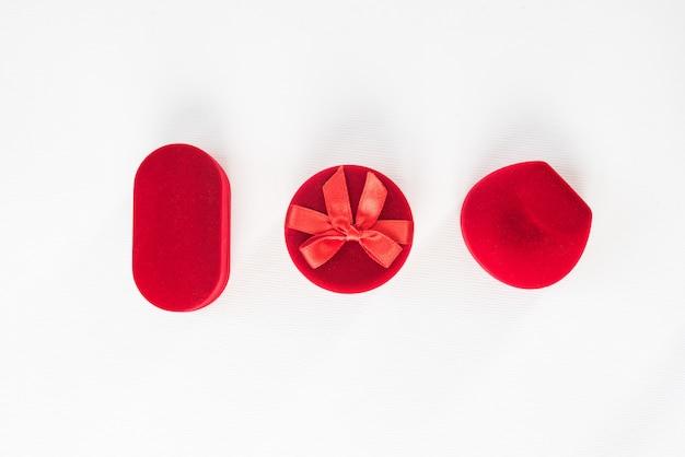 Trzy czerwone zamknięte pudełka z biżuterią na białym tle