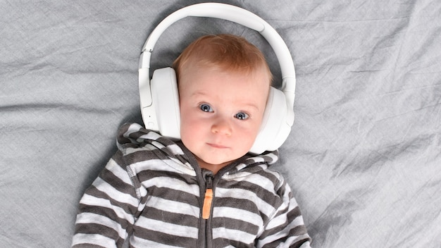 Trzy-cztery miesiące słodkie kaukaski dziecko leżące na łóżku, słuchając muzyki w dużych słuchawkach.