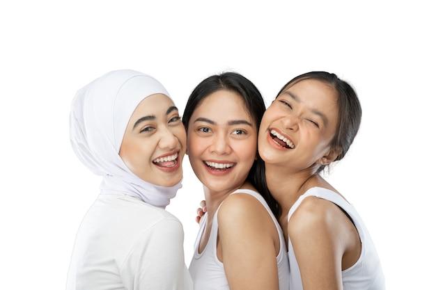 Trzy czułe azjatyckie kobiety w ścisłym uścisku, śmiejąc się i uśmiechając