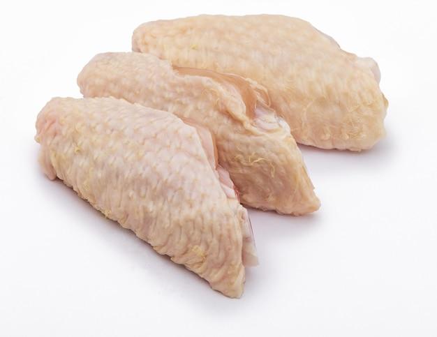 Trzy czyste surowe skrzydełka z kurczaka, na białym tle.