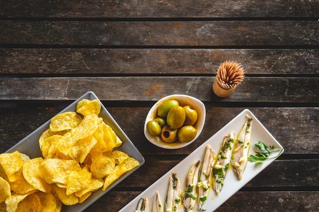 Trzy dania z frytkami, zerwanymi anchois i zielonymi oliwkami na ciemnym drewnianym stole z wykałaczkami. typowe hiszpańskie przekąski.