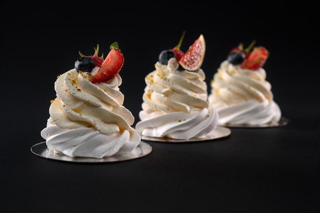 Trzy desery mascarpone w rzędzie ozdobione plastrami fig, truskawkami, jagodami i malinami. świeże pyszne bita śmietana z jagodami na białym tle na czarnym tle.