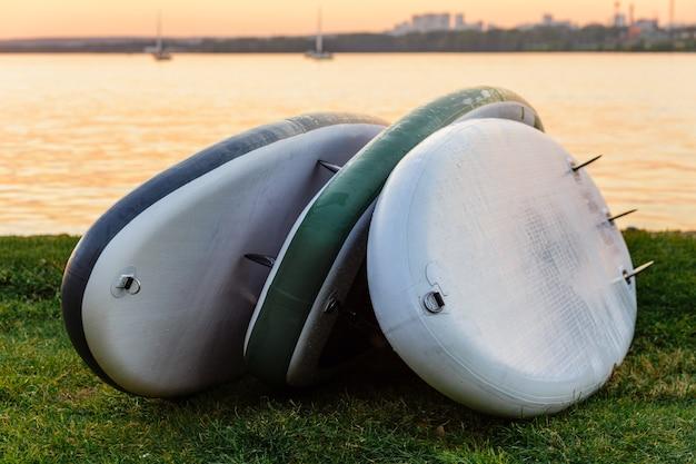 Trzy deski sup leżące na trawie nad jeziorem lub morzem