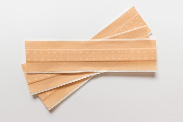 Trzy długie medyczne plastry antyseptyczne w kolorze beżowym do pokrywania drewna.