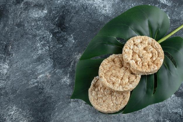 Trzy dmuchane ciastka ryżowe na zielonych liściach