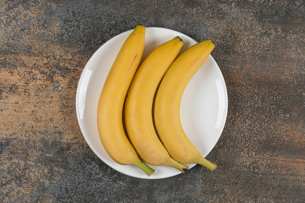 Trzy dojrzałe banany na białym talerzu