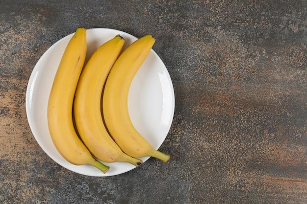 Trzy dojrzałe banany na białym talerzu.