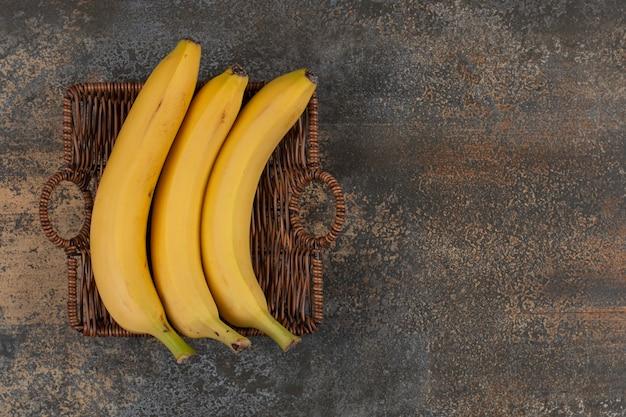 Trzy dojrzałe banany w drewnianym koszu.