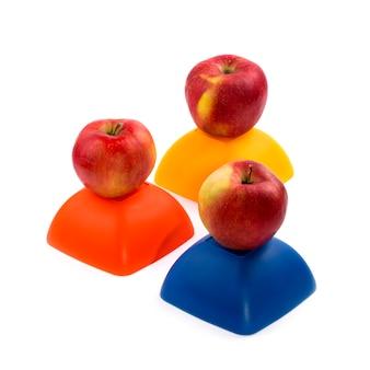 Trzy dojrzałe czerwone jabłka na żółtej, czerwonej i niebieskiej figurze