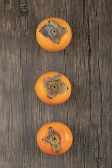 Trzy dojrzałe owoce persimmon umieszczone na drewnianej powierzchni