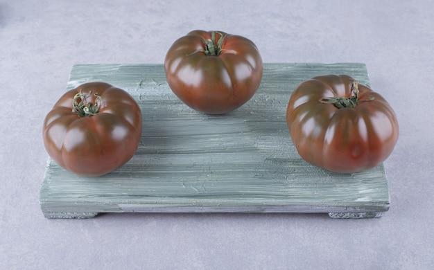 Trzy dojrzałe pomidory na desce.